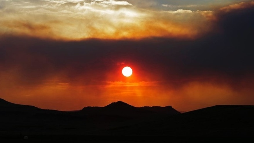 June 23, 2013: The sun sets through wildfire smoke, near Monte Vista, Colo. A large wildfire near a popular summer retreat in southern Colorado continues to be driven by winds and fueled by dead trees in a drought-stricken area, authorities said.