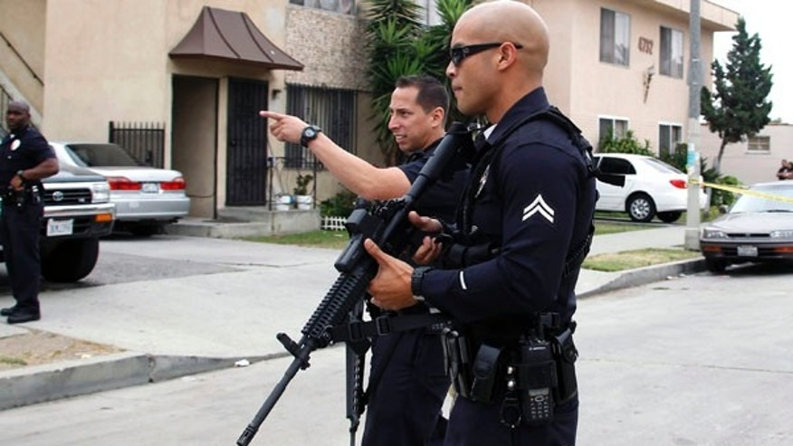 June 25, 2013: Los Angeles police officers close off and search a city street after two police officers were shot and wounded in an attack outside a police station in the Mid-City area of Los Angeles.  A black-clad gunman ambushed two detectives returning to a police station early Tuesday, but they received only minor injuries and were helping in the hunt for the attacker, police said.