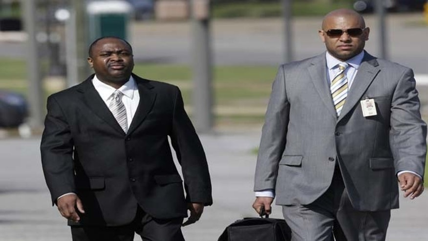 Former Ventress Correctional Facility Lt. Michael Smith, left, arrives at the Federal Building in Montgomery, Ala., with his attorney Stephen Ganter on Tuesday