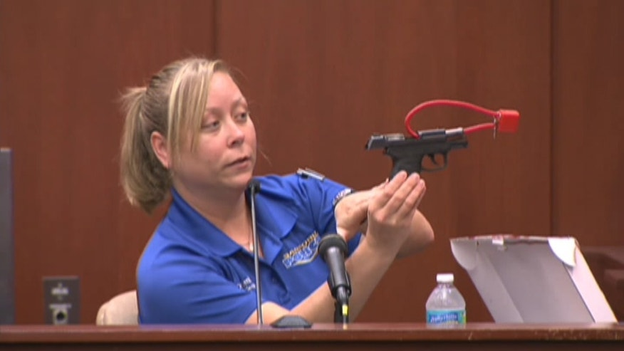 Sanford Police Department crime scene technician Diana Smith holds up a gun belonging to George Zimmerman.