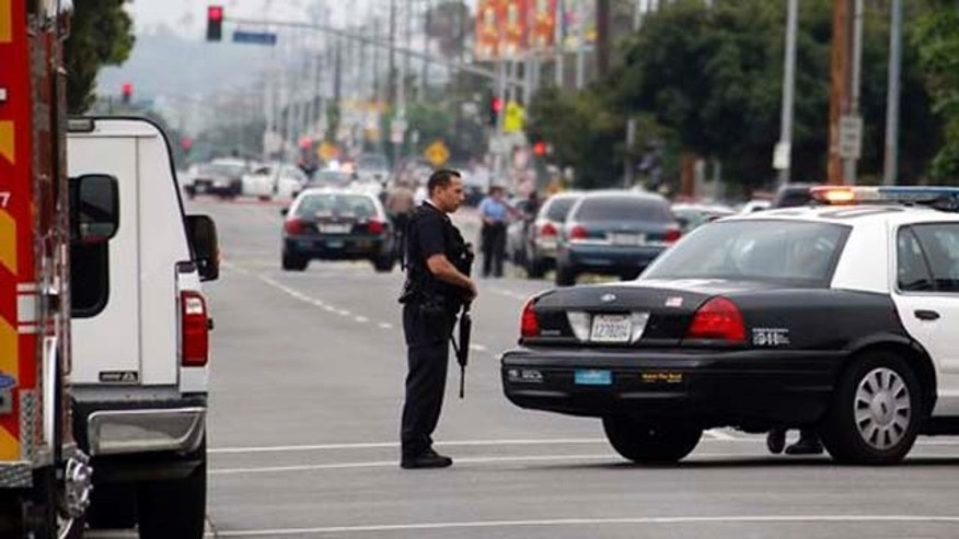 June 25, 2013: Los Angeles police officers close off and search a city street after two police officers were shot and wounded in an attack outside a police station in the Mid-City area of Los Angeles.