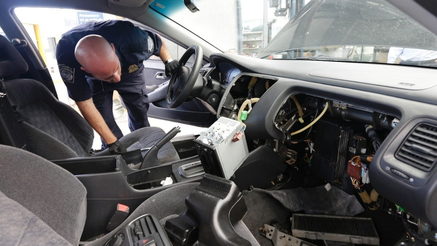 June 27, 2013: Customs and Border Protection officer Steve Delgado looks in at the dismembered dashboard of a Honda Accord after finding more than 14 pounds of methamphetamine hidden behind the radio at the San Ysidro port of entry in San Diego.