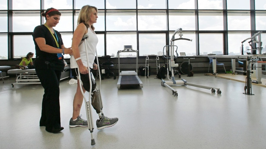 June 20, 2013: With physical therapist Dara Casparian, left, guiding her strides, Boston Marathon bombing survivor Roseann Sdoia, of Boston, looks forward towards a mirror at the Spaulding Rehabilitation Hospital, Friday June 20, 2013, in Boston.