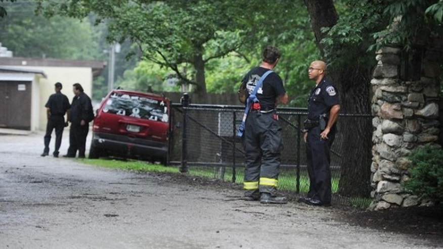 June 29, 2013: A firefighter and a policeman confer at the scene of a lightning strike that caused injuries at 9300 Moore Road in Indianapolis.