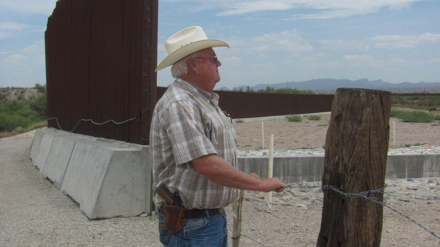 Hudspeth County Sheriff Deputy Johnny Schuller stands next to a source of frustration for residents in the area where the border security fence comes to a dead end in the middle of the desert leaving four strands of barbed wire to separate the U.S. from Mexico.