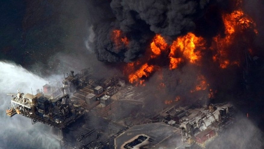 In this April 21, 2010 file aerial photo, the Deepwater Horizon oil rig burns in the Gulf of Mexico more than 50 miles southeast of Venice, La.