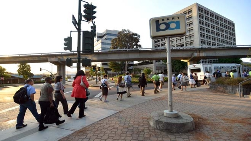 July 2, 2013: Commuters work their way down California Boulevard to a line of buses waiting to take them to San Francisco on the second day of the BART strike in Walnut Creek, Calif.