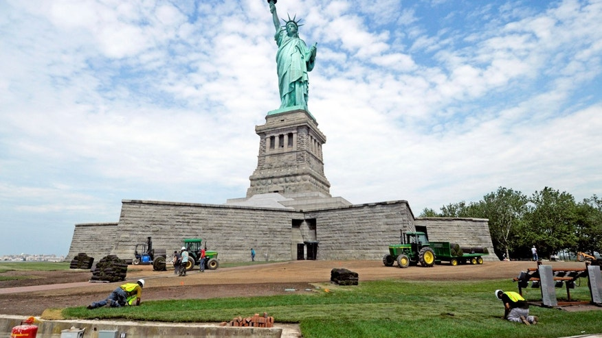 June 26, 2013: In this photo provided by the National Park Service, workers on Liberty Island install sod around the national monument which is set to re-open on the 4th of July, in New York.