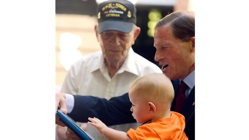 July 5, 2013: Sen. Richard Blumenthal, D-Conn., right, presents U.S. Navy WWII veteran Frank Bennett with a Purple Heart medal with 1-year old Axel Trygg Bennett at his home in Ledyard, Conn.