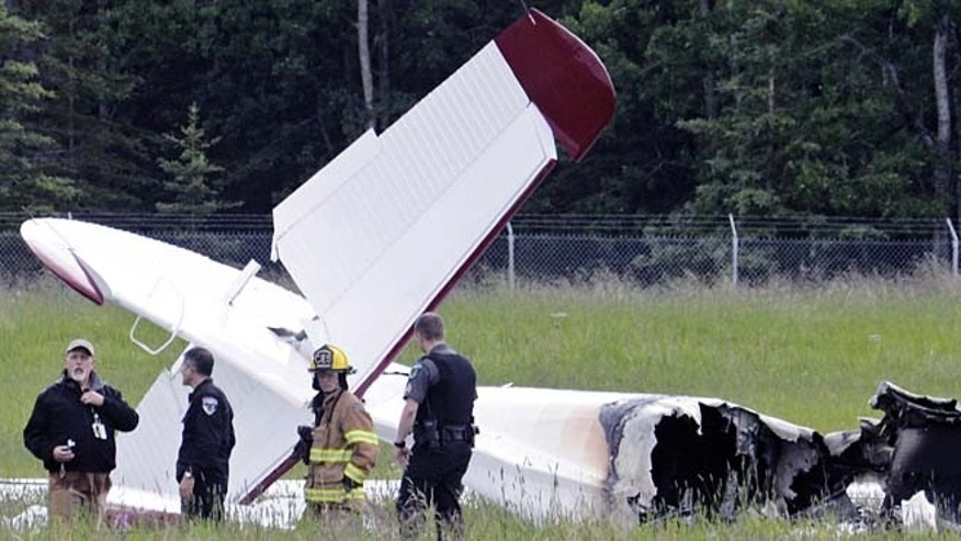 July 7, 2013: Police and emergency personnel stand near the remains of a fixed-wing aircraft that was engulfed in flames at the Soldotna Airport in Soldotna, Alaska.