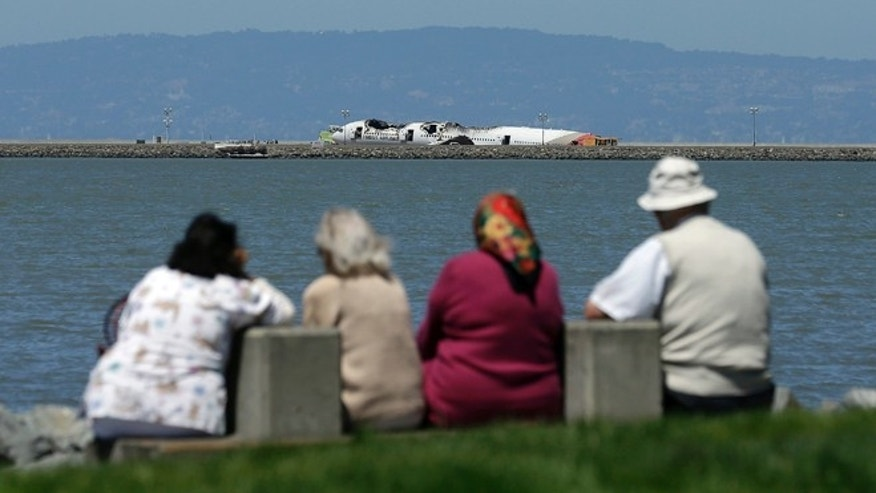 July 8: Spectators look toward the wreckage of Asiana Airlines Flight 214 that crashed upon landing Saturday at San Francisco International Airport.