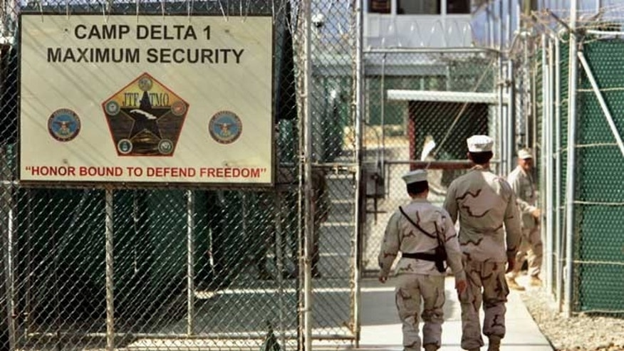 June 27, 2006: This photo, reviewed by a U.S. Department of Defense official, U.S. military guards walk within Camp Delta military-run prison, at the Guantanamo Bay U.S. Naval Base, Cuba.