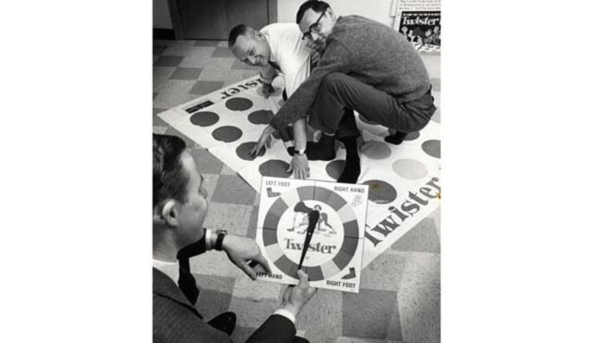 "Dec. 16,1966: In this photo, co-inventors of the game ""Twister"" Charles Foley, left, and Neil Rabens demonstrate the game for Charles McCarty, foreground, president of Research and Development, Inc., in Minnesota."