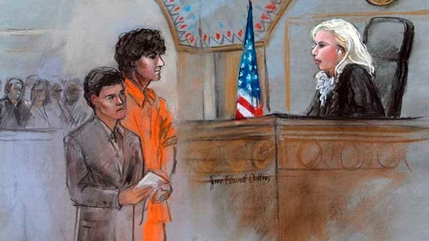 July 10, 2013: This courtroom sketch depicts Boston Marathon bombing suspect Dzhokhar Tsarnaev standing with his lawyer Judy Clarke, left, before Magistrate Judge Marianne Bowler, right, during his arraignment in federal court in Boston.