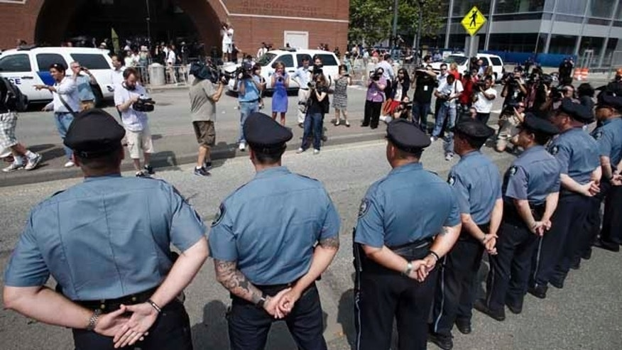 July 10, 2013: MIT police officers stand at attention outside the federal courthouse prior to arraignment for Boston Marathon bombing suspect Dzhokhar Tsarnaev in Boston.