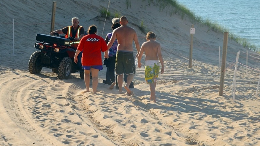 July 12, 2013: In this photo, family members of an 6-year-old boy who was buried in the sand at Mount Baldy are escorted to the beach by a Michigan City Police Department chaplain in Michigan City, Ind. as heavy equipment is used to try to find their child.