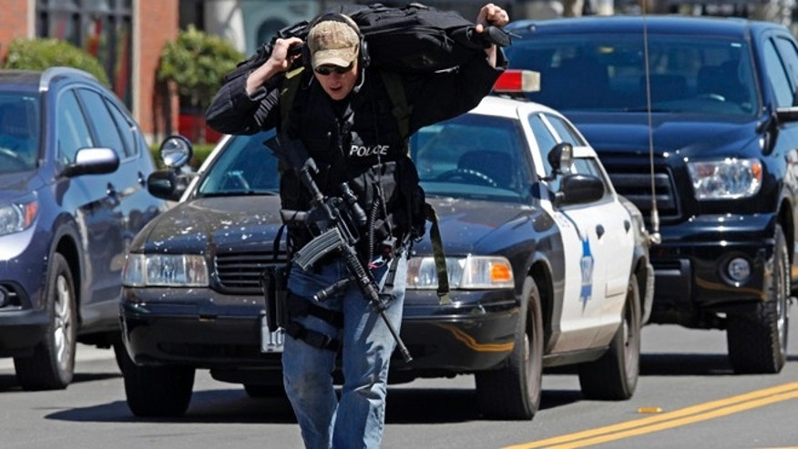 July 12, 2013: A police officer carries weapons down Eighth Street toward the scene of a shooting in San Francisco.