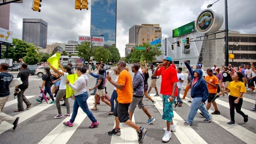 July 14, 2013: Demonstrators cross Marietta Street as they march in protest the day after George Zimmerman was found not guilty in the 2012 shooting death of teenager Trayvon Martin, in Atlanta.