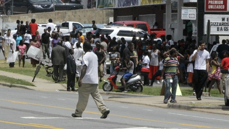 July 15, 2013: A man walks past a crowd gathered near the site of a fatal shooting in Little Rock, Ark.. A man was shot by Little Rock police after he ran following a traffic stop that officers made because the man was driving an allegedly stolen SUV. (AP Photo/Danny Johnston)