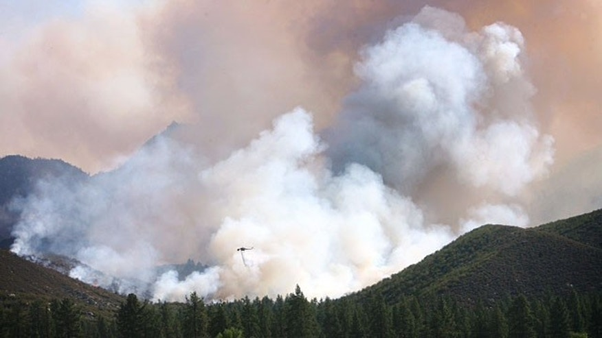 July 16, 2013: A water-dropping helicopter is dwarfed by the smoke rising from the Mountain Fire wildfire burning near Mountain Center, Calif. A fast-moving wildfire in the mountains west of Palm Springs nearly doubled in size Tuesday, prompting the evacuation of about 50 homes. (AP Photo/The Press-Enterprise,Kurt Miller )