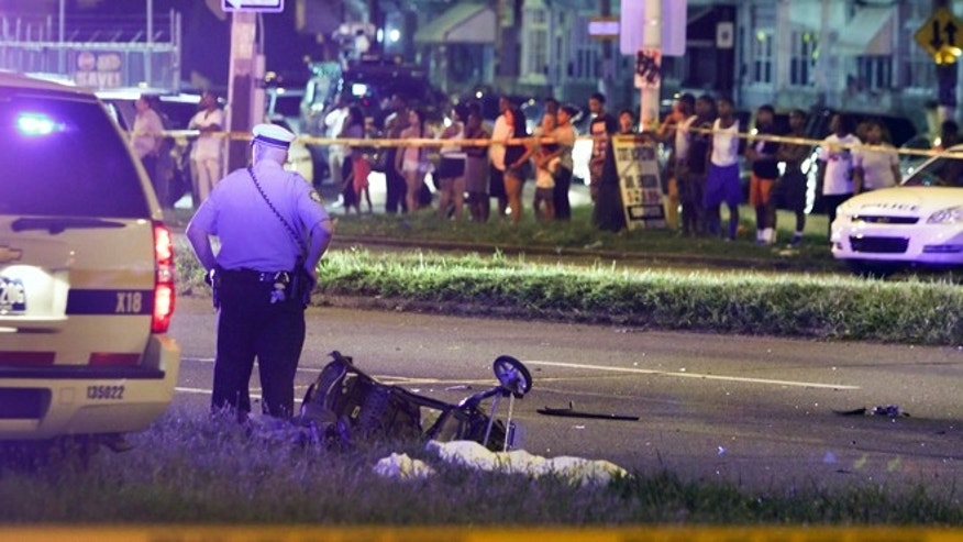 July 16, 2013: A police officer stands by a sheet covering the remains of a young child and a baby stroller at the scene of a fatal accident on Roosevelt Boulevard in the Olney section of Philadelphia on Tuesday. Philadelphia police are investigating whether cars may have been drag racing when a mother and two young sons were struck and killed attempting to cross a busy highway. (AP/Joseph Kaczmarek)