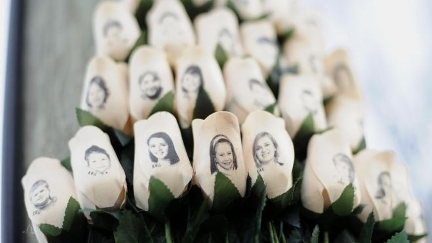 Jan. 14, 2013: White roses with the faces of victims of the Sandy Hook Elementary School shooting are displayed on a telephone pole near the school on the one-month anniversary of the mass shooting that left 26 dead, including 20 children in Newtown, Conn.