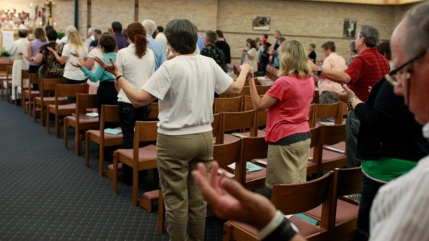 July 19, 2013: Worshipers pray, some holding hands, during a memorial mass held for supporters and families of those killed in the Aurora movie theater shootings, at St. Michael the Archangel Catholic Church, in Aurora, Colo.