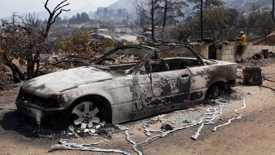 July 18, 2013: The charred remains of a car are shown after a wildfire passed through the area of Lake Hemet, Calif. (AP Photo/Nick Ut)