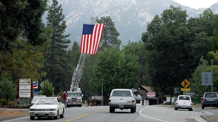 July 21, 2013: A ladder truck flies the American flag to greet residents back to Idyllwild after the evacuation order was rescinded in the areas affected by the Mountain Fire. (AP Photo)