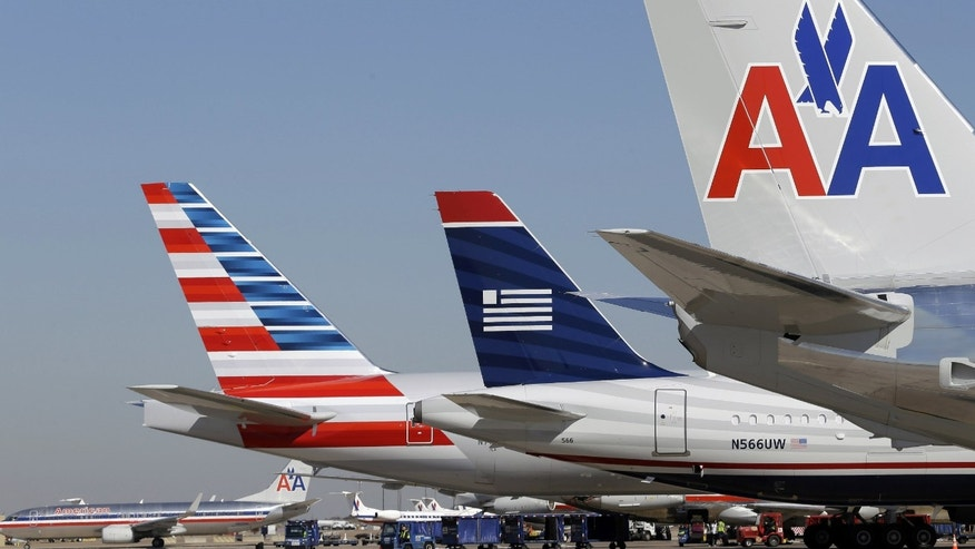 U.S. Airways and American Airlines planes are shown at gates at DFW International Airport in Grapevine, Texas.