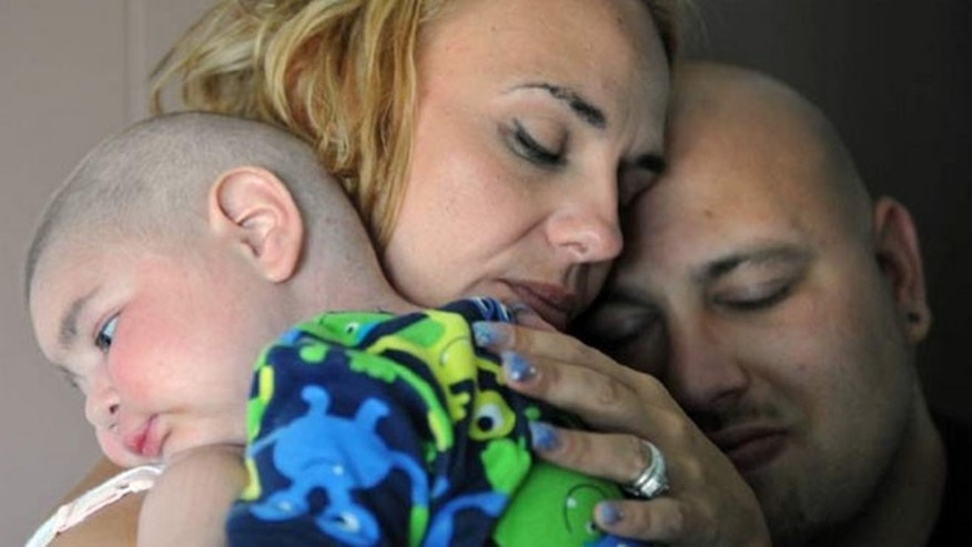 July 30: Christine Swidorsky holds her son, Logan Stevenson, 2, with her husband-to-be and Logan's father, Sean Stevenson