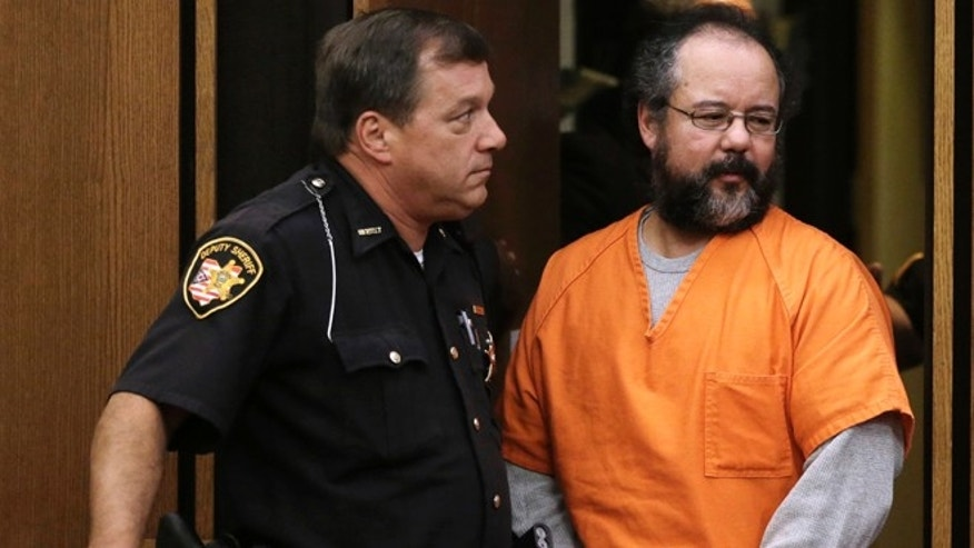 July 26, 2013: Ariel Castro, right, walks into the courtroom watched closely by a deputy sheriff in Cleveland. Castro