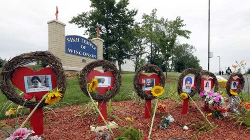 August 5, 2013: A makeshift memorial is seen before a candlelight vigil in the parking lot the Sikh Temple of Wisconsin in Oak Creek, Wis. Monday is the one-year anniversary of the shooting rampage when a white supremacist at the temple where six people were killed. (AP Photo/