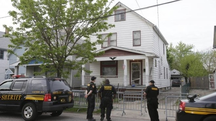 FILE: May 7, 2013: Sheriff deputies stand outside a house in Cleveland, the day after three women who vanished a decade ago were found there.