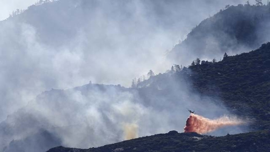 August 9, 2013: An air tanker drops fire retardant on a hot spot as firefighters continue to battle a wildfire near Banning, Calif.