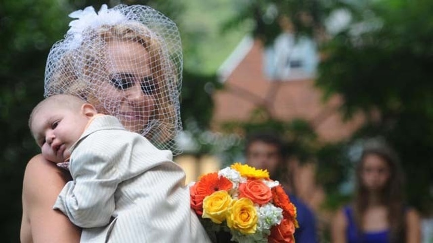 In this Aug. 3, 2013 file photo, Christine Swidorsky carries her son and the couple's best man, Logan Stevenson, 2, down the aisle to her husband-to-be Sean Stevenson during the wedding ceremony in Jeannette, Pa. (AP Photo)