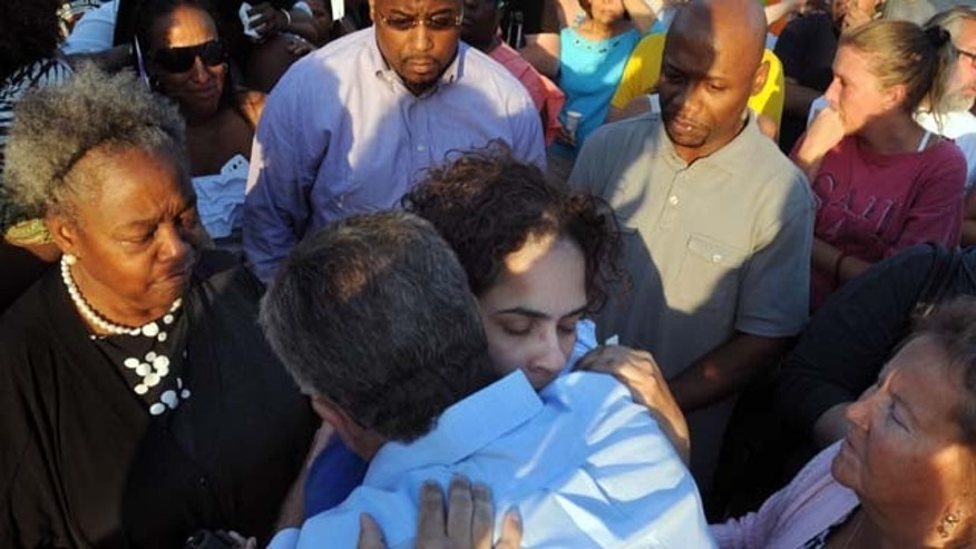 August 10, 2013: Joann Mitchell, the mother of one of the crash victims, hugs East Haven Mayor Joseph Maturo, during a vigil in East Haven, Conn. (AP Photo)
