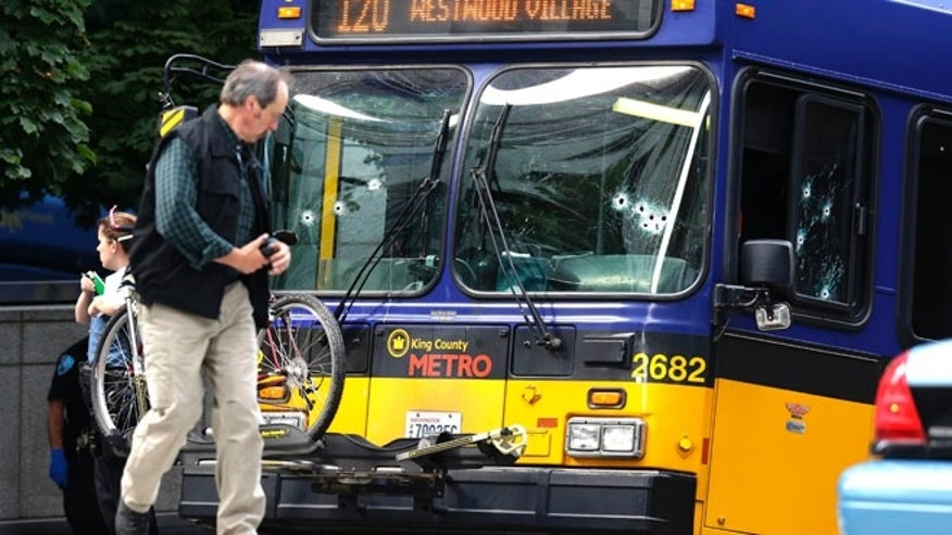 Aug. 12, 2013: An official walks next to a King Co. Metro bus with multiple bullet holes in its windshield and side window, after a bus driver was shot Monday in downtown Seattle. A man who had shot the driver of another bus was shot by officers after he boarded the bus shown here.