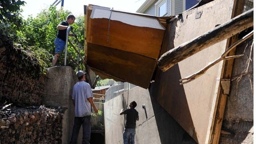 August 10, 2013: From left, Dan McCormack, Chris Lambrite Jr., and Chris Lambrite work to remove three sides of a cottage from a drainage after the entire building was ripped off its foundation by a flash flood that hit Manitou Springs, Colo.