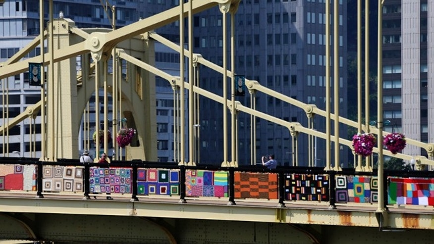 Aug. 12, 2013: Pedestrians walk across the Andy Warhol bridge in downtown Pittsburgh. More that 1,800 knitters have covered the bridge in 3,000 feet of colorful yarn. Volunteers worked all weekend to attach 580 blanket-sized, hand- knitted panels to the pedestrian walkways. Organizers say it is the nation's largest yarn bomb. (AP/Gene J. Puskar)