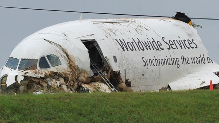 Aug 16, 2013: The National Transportation Safety Board and FBI scour a field, north of the Birmingham-Shuttlesworth International Airport where UPS flight 1354 crashed on Wedesday,  in Birmingham, Ala.