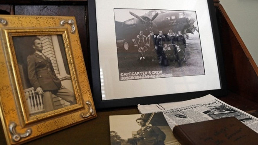 Aug. 16, 2013: This photo taken in Raleigh, N.C., shows memorabilia from U.S. Army Air Corps 2nd Lt. David C. Cox's military service during World War II including his portrait and members of his B-17 crew. Lt. Cox traded his gold aviator ring for a couple of chocolate bars while he was imprisoned in a German prisoner of war camp. The ring was returned to Cox's son David Cox Jr. by a German couple through some investigative help from an American neighbor.