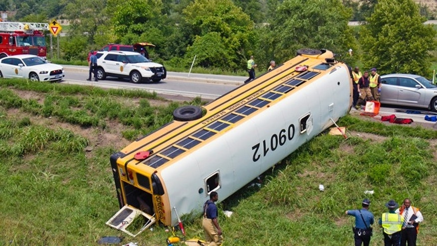 Aug 21, 2013: Officials investigate the scene of a school bus accident, in Bonner Springs, Kan. One of two buses taking Missouri sixth-graders to an annual campout overturned in northeast Kansas on Wednesday, injuring at least 20 of those onboard, including the driver.