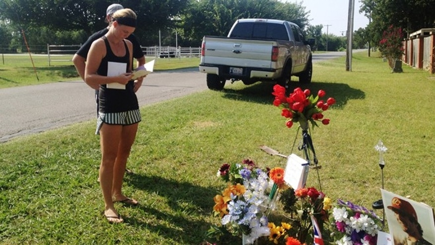 Aug. 16, 2013: Sarah Harper,Christopher Lane's girlfriend, stands beside a memorial along the road where police say Lane, an Australian baseball player was shot and killed by three bored teenagers who decided to kill someone for fun, in Duncan, Okla. Lane, who was visiting Duncan where Harper and her family lives, had jogged past a home where the boys were staying and that apparently led to him being gunned down at random, said Police Chief Danny Ford.