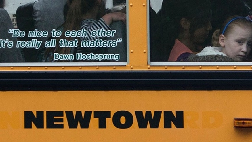 June 14, 2013: Students sit behind a quote by slain Sandy Hook Elementary School principal Dawn Hochsprung, displayed on the window of a school bus, as it approaches a stop near the original site of Sandy Hook Elementary School in Newtown, Connecticut.