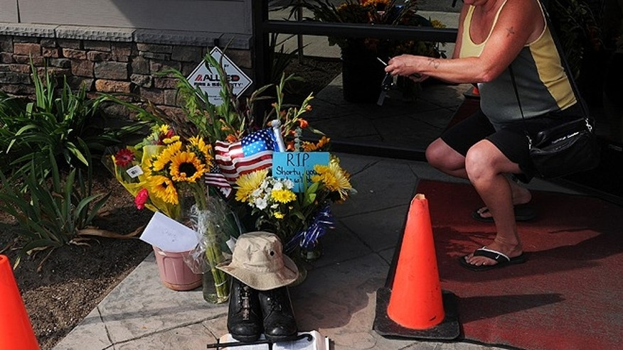 Aug. 22, 2013: Lill Duncan takes a photo of a memorial for Delbert Belton, an 88-year-old World War II veteran who was beaten to death, in Spokane, Wash. Police have arrested one of two teens suspected of fatally beating Belton, who had survived the battle for Okinawa, and the police chief said Friday, Aug. 23, that the brutal attack does not appear to have been racially motivated. (AP/The Spokesman-Review, Tyler Tjomsland)
