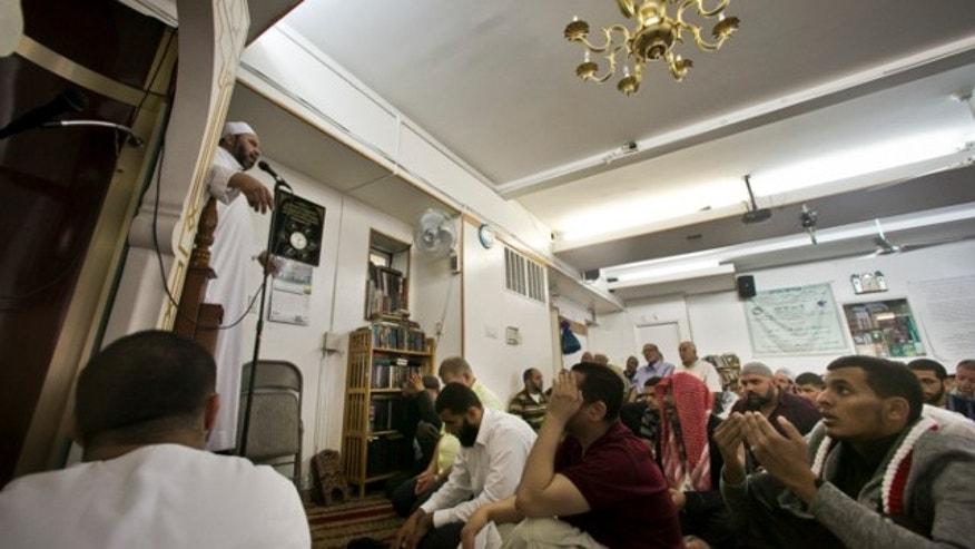 Aug. 16, 2013: Dr. Muhamad Albar, far left, speaks to a congregation during Jumu'ah prayer service at the Islamic Society of Bay Ridge mosque in the Brooklyn borough of New York.