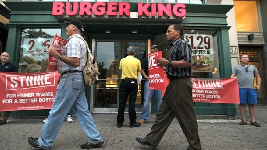 Aug. 29, 2013: Protesters display placards outside a Burger King fast food restaurant in Boston. The protest was one of several planned in Boston Thursday in what organizers say are similar walkouts planned in dozens of cities to push chains such as McDonald's, Taco Bell and Wendy's to pay workers more.