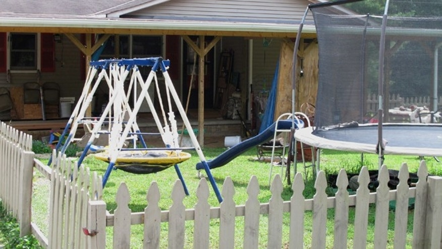 Aug 29, 2013: Playground equipment sits outside the home near London, Ky., where Ernest Chris Chumbley says he fatally shot his wife because she asked him to end her suffering from terminal cancer.