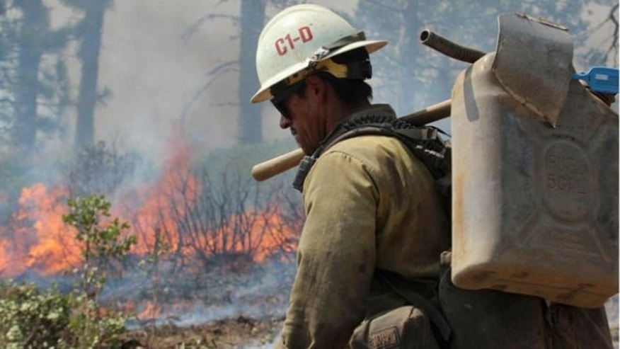 Aug. 30, 2013: A member of the Monterey Hotshots carries a gas can near a burn operation on the southern flank of the Rim Fire near Yosemite National Park in California.